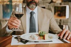 吃午餐和喝红葡萄酒的英俊的有胡子的商人 免版税库存图片
