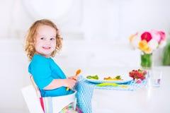 吃午餐的小美丽的女孩沙拉 库存照片