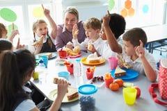 吃午餐的小组孩子在学校食堂 免版税库存照片