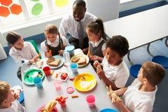 吃午餐的小组孩子在学校食堂 库存照片