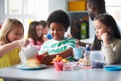 吃午餐的小组孩子在学校食堂 免版税图库摄影