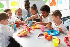 吃午餐的小组孩子在学校食堂 库存图片