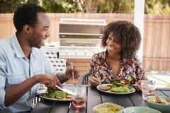 吃午餐的年轻黑夫妇在一张桌上在庭院里 免版税库存照片