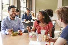 吃午餐的老师和学生在高中自助食堂在休息期间 免版税图库摄影