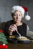 吃单独圣诞晚餐的哀伤的妇女 库存图片