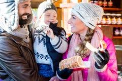 吃卷和香肠在圣诞节市场上的家庭 免版税库存照片