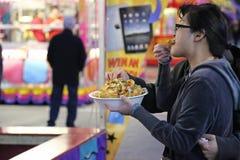 吃卷曲油炸物的人们在西海岸娱乐狂欢节 库存图片
