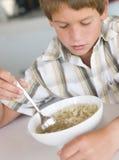 吃厨房汤年轻人的男孩 免版税库存照片