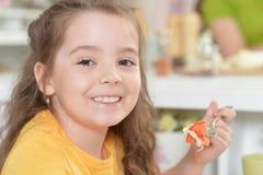 吃可口新鲜的沙拉的逗人喜爱的女孩 免版税库存图片
