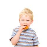 吃可口曲奇饼的逗人喜爱的小男孩被隔绝 免版税库存图片