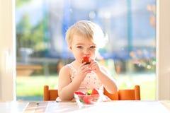 吃可口草莓的小女孩 免版税库存图片