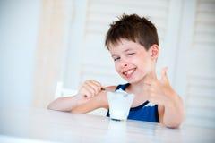 吃可口酸奶的微笑的小男孩 库存照片