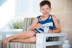 吃可口酸奶的微笑的小男孩 免版税库存图片