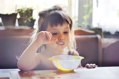 吃可爱的小女孩画象午餐 免版税库存照片