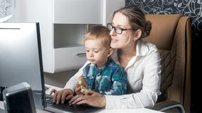 吃可爱的小孩的男孩画象,当他的工作在办公室时的母亲 免版税库存照片