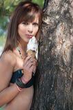 吃和享用她的冰淇凌的夫人 免版税库存照片