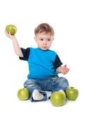 吃和使用用绿色苹果的逗人喜爱的男婴孩子 库存图片