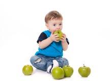 吃和使用用绿色苹果的逗人喜爱的男婴孩子 免版税库存照片