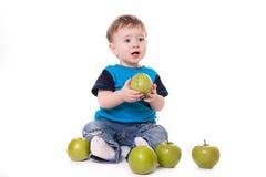 吃和使用用绿色苹果的逗人喜爱的男婴孩子 免版税库存图片