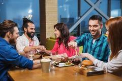 吃和品尝食物的朋友在餐馆 免版税图库摄影