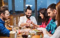 吃和品尝食物的朋友在餐馆 免版税库存照片