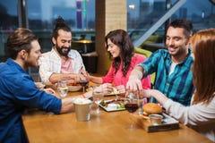 吃和品尝食物的朋友在餐馆 图库摄影