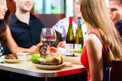 吃和喝在快餐吃饭的客人的朋友 免版税图库摄影