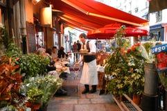 吃和喝在巴黎街道餐馆的人们  图库摄影
