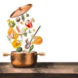 吃和烹调与各种各样的飞行的健康素食主义者砍了菜成份,烹调罐和匙子在木桌d上 免版税库存照片