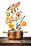 吃和烹调与各种各样的飞行的健康素食主义者砍了菜成份,烹调罐和匙子在木桌d上 库存照片