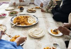 吃回教的家庭在地板上的晚餐 免版税库存图片