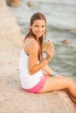 吃圆锥形的冰淇淋杯的一名新美丽的妇女的纵向 免版税图库摄影
