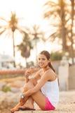 吃圆锥形的冰淇淋杯的一名新美丽的妇女的纵向 免版税库存照片