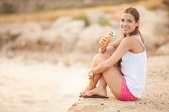 吃圆锥形的冰淇淋杯的一名新美丽的妇女的纵向 图库摄影