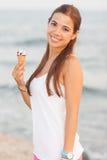 吃圆锥形的冰淇淋杯的一名新美丽的妇女的纵向 免版税库存图片