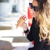 吃圆锥形的冰淇淋杯的逗人喜爱的微笑的妇女 免版税库存图片