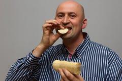 吃土豆片和看照相机的年轻快乐的人 库存照片