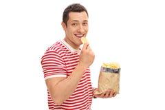 吃土豆片的年轻快乐的人 免版税库存照片
