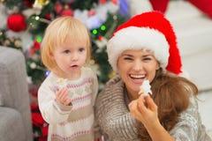 吃圣诞节曲奇饼的微笑的母亲和婴孩 库存图片
