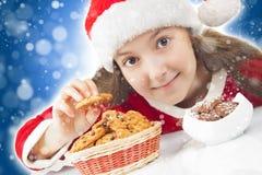 吃圣诞节曲奇饼的愉快的圣诞节女孩 免版税库存图片