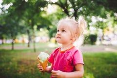 吃在一个奶蛋烘饼杯子的小滑稽的女孩金发碧眼的女人甜蓝色冰淇凌在绿色夏天背景在公园 抹上她的面孔 图库摄影