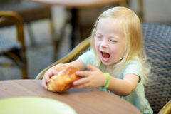 吃在一个室外咖啡馆的可爱的小女孩一个小圆面包 免版税库存照片