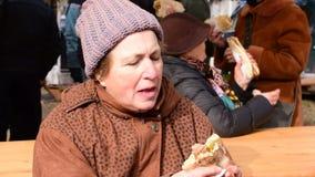 吃在一个小圆面包的老妇人一根自创猪肉香肠与她的手指户外,猪屠杀节日 影视素材