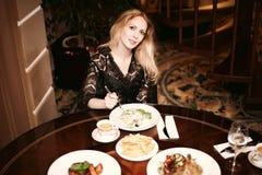 吃在一个餐厅的美丽的妇女 库存图片