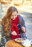 吃在一个巴黎人咖啡馆的女孩奶蛋烘饼 免版税库存照片