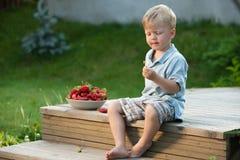 吃在一个晴朗的甲板的孩子草莓 免版税库存照片