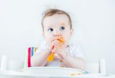 吃在一张白色高脚椅子的甜杂乱婴孩一棵红萝卜 库存图片