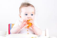 吃在一张白色高脚椅子的甜婴孩一棵红萝卜 图库摄影
