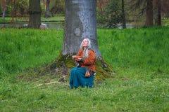 吃在一棵树下的幻想形象在公园在矮子Fantas 免版税图库摄影