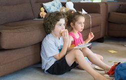 吃在休息室地板的兄弟姐妹三明治 免版税库存图片